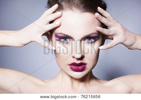 Beautiful brunette woman with creative make up violet eye shadows full red lips, blue eyes and curly