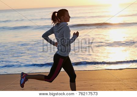 woman running on beach in morning sunrise fitness workout sport