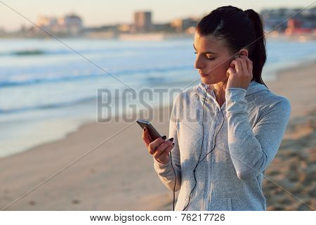woman with smartphone and earphones choosing music for morning workout fitness run