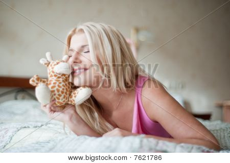 young pretty woman relaxing on the bed with a little toy