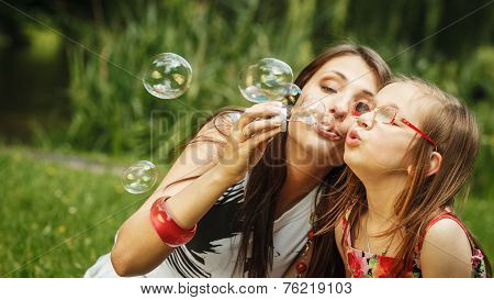 Mother And Little Girl Blowing Soap Bubbles In Park.