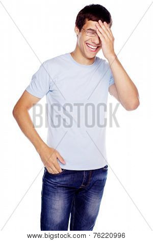 Laughing young man in glasses and blue shirt with hand on his face isolated on white background