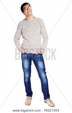 Full length portrait of young man in glasses and beige sweater with hands in his jeans pockets smiling and looking up on isolated on white background