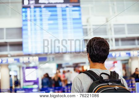 Young man with backpack in airport near flight timetable