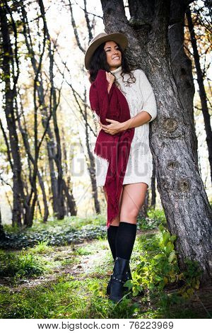 smiling young woman wearing hat,  red wool scarf and wool dress enjoy in autumn sunny day outdoor shot in wood full body shot