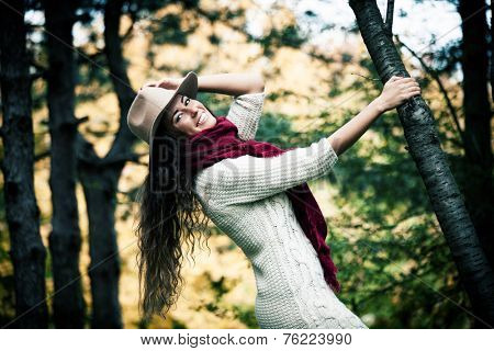happy young woman wearing hat,  red wool scarf and wool dress enjoy in autumn  day outdoor shot in forest