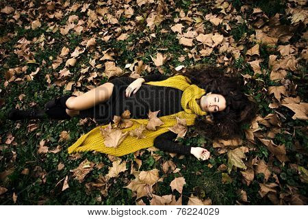 beautiful woman with eyes closed  lie in grass and autumn leaves wearing dark green dress and long yellow wool scarf full body shot