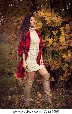 smiling young woman wearing leather high heel long boots,  red wool scarf and wool dress outdoor shot autumn day in park