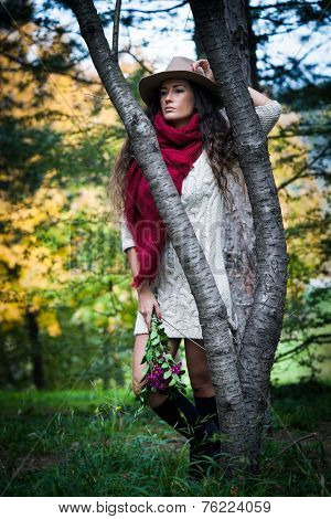 young woman wearing hat,  red wool scarf and wool dress  outdoor shot in wood hold flowers in hand full body shot