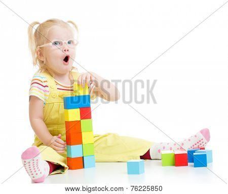 Funny kid in eyeglases making tower using blocks with letters isolated on white