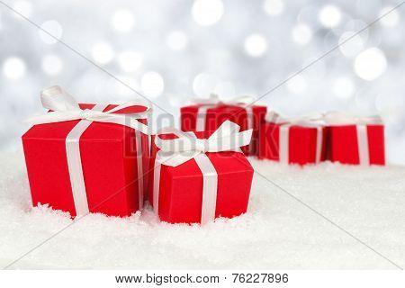 Gift boxes in snow with twinkling lights