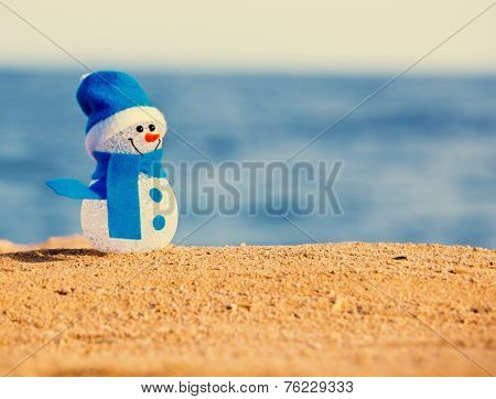 Snowman on sand near sea. Christmas decoration. Vacations