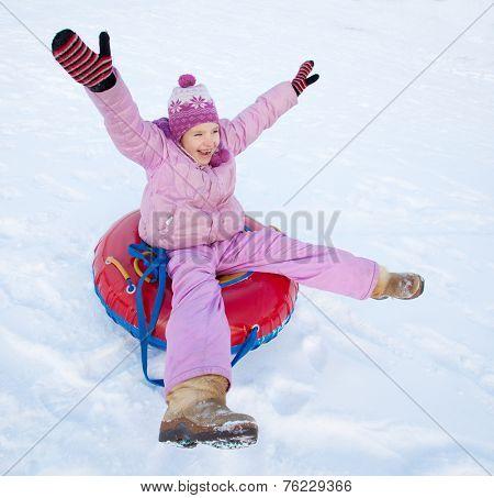 Child sledding in winter hill. Happy girl tobogganing