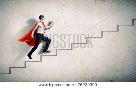 Young superman walking up the stair case