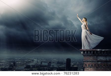 Young woman in in darkness reaching to sun light