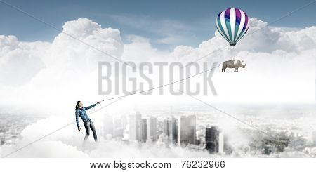 Young girl in casual holding colorful aerostat on rope