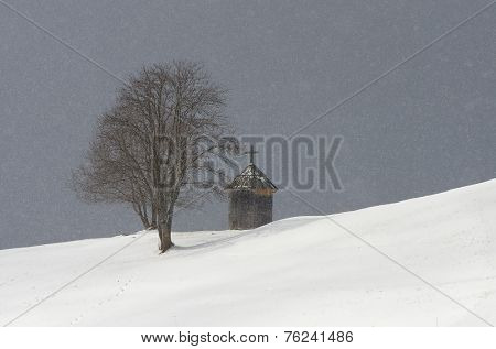 Winter landscape with snowfall. Wooden chapel and a tree on a hill. Mountain village. Carpathians, Ukraine, Europe