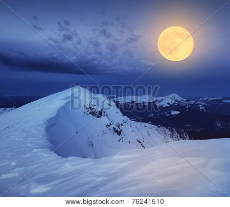 Winter landscape. The top of the rocky mountains. Night and the light of the full moon. Carpathian mountains, Ukraine, Europe