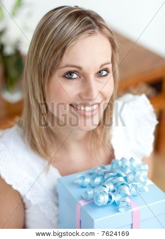 Cheerful Young Woman Holding A Present Sitting On The Floor
