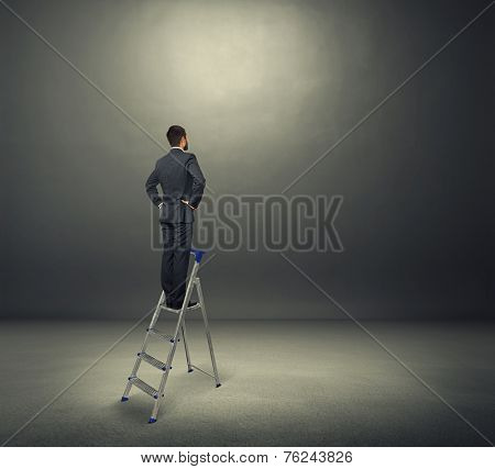 concentrated businessman standing on the stepladder and looking forward. photo in the dark room
