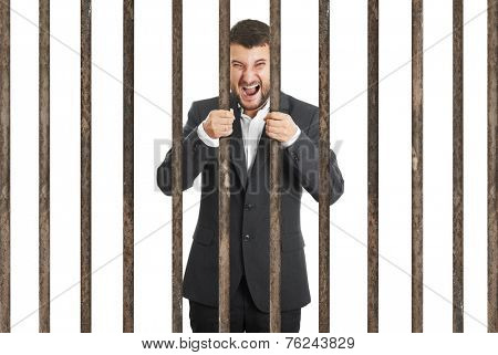 angry screaming businessman behind the prison cell over white background