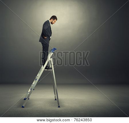 displeased businessman in black suit standing on the stepladder and looking down. photo in the dark room