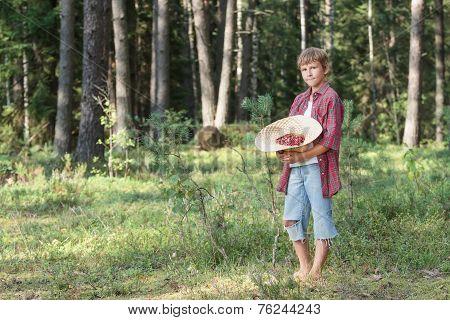Teenage Boy Holding Hat Full Of Red Wildberries