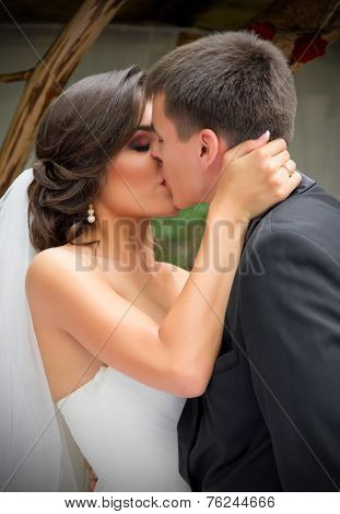 Young newlyweds kissing and summer day