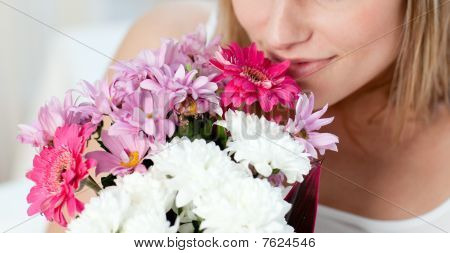 Close-up Of A Woman Smelling A Bunch Of Flowers