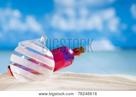glitter christmas glass ball and bottle on  beach with seascape background