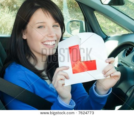 Happy Teen Girl Sitting In Her Car Tearing A L-sign