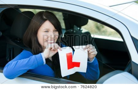 Joyful Teen Girl Sitting In Her Car Tearing A L-sign
