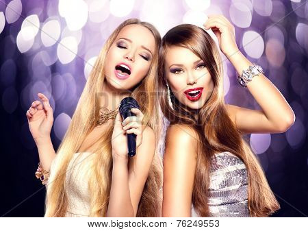 Karaoke party. Beauty girls with a microphone singing and dancing over holiday blinking background. Disco party. Celebration