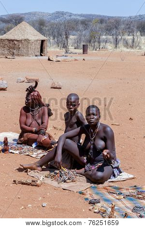 Himba And Zemba Girl With Souvenirs For Sale In Traditional Village