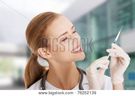Beautiful young doctor with needle.