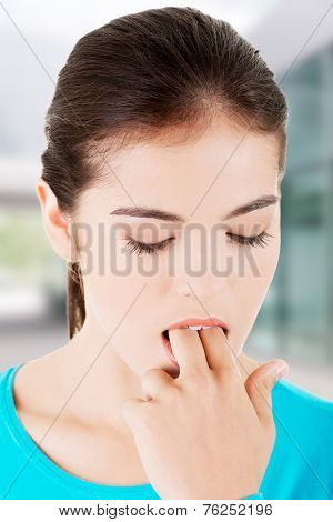 Woman putting her finger in mouth to provoke vomiting.