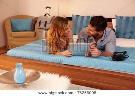 Happy young couple lying on bed in hotel room, using tablet pc.