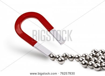 Magnet attracting chrome ball bearing concept for marketing, business leadership or attracting clients