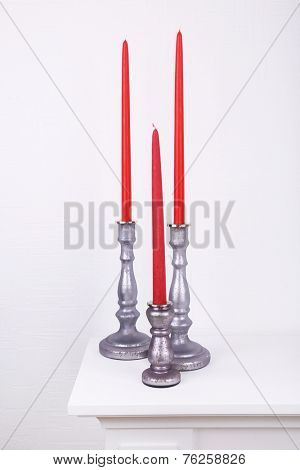 Red candles in candle holders on table on white background