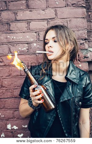 Bad Young Woman Lighting Up A Cigarette From Molotov Cocktail Bomb In Her Hand