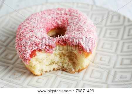 Bitten delicious donut on plate close-up
