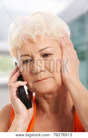 Old lady talking through phone, receiving bad news.