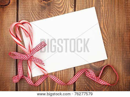 Christmas greeting card or photo frame over wooden table with candy canes. View from above