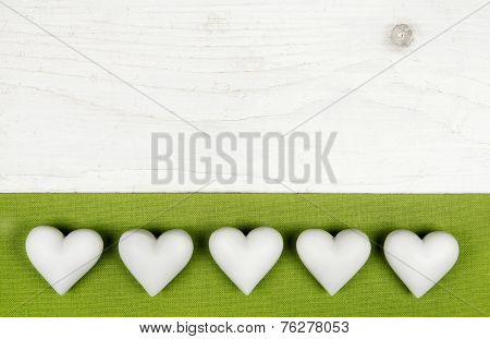 Five white hearts on wooden white shabby chic background with apple green frame.