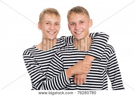 Cheerful twin brothers in a striped shirts isolated on white background