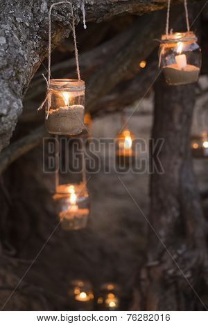 Beautiful decorated romantic place for a date with jars full of candles hunging on tree at night