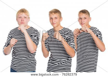 Young men in striped shirt standing in a pose of a boxer. Two of the boys twin brothers.