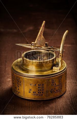 Vintage retro compass with sundial on old wooden background