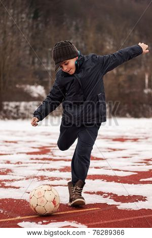 boy kicking the ball in winter