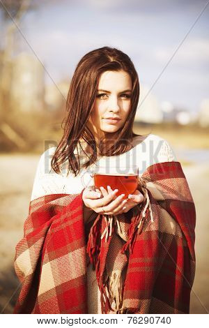 Brunette woman in plaid on a park near lake drenking tea. autumn weather. cold.